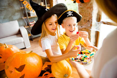 Very cheerful excited kids in carnival head wear, with treats, rear cropped view of blond mom with bowl of colorful treats, carved pumpkins near them on the desk top