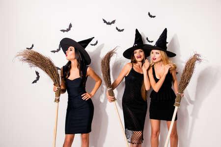 Trio hete mysterieuze enge elegante tovenaars, bezems houden, doe toveren, blazen met geploegde rode lippen, doen duivel duivel demon magie, grijnzend, samen genieten, op achtergrond met vleermuizen