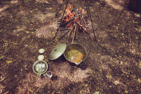 High angle view of a soup in a kettle, near the camp fire in a camp site, crockery for two, on a ground and dry leaves in a forest