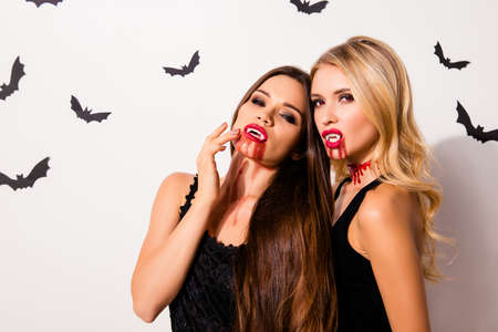 Terrifyng nightmare. Close up portrait of cruel paranormal witches with angry expression and mouthes with dripping blood, in dark dresses, isolated on white background with small mystical bats Imagens