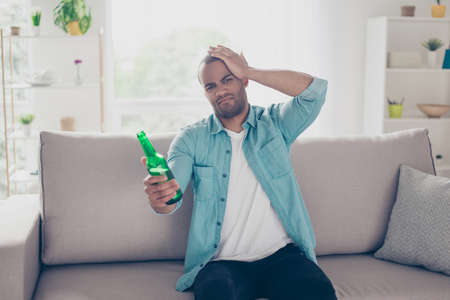Upset young african man is frustrated about the loss of the team in game he is watching on tv. Guy is having beer and sitting on the sofa at living room at home