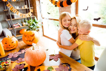 Lovely family cuddling, mum with two small blonde cheerful kids in decorated nice loft light room at home, desktop with cutted handmade pumpkins, colorful candies, fall leaves, garlands on window