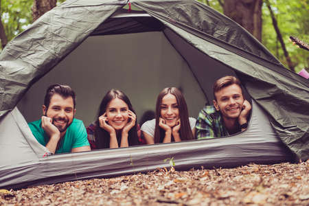 So fun together! Two lovely couples lying down in the tent in a campground, so happy, smiling, relaxing and enjoying Stock fotó