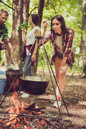 Close up cropped photo of young cute brunette girl, checking the meal in cattle, cooking on a flame, tasting it, friends are having beer behind Stock Photo