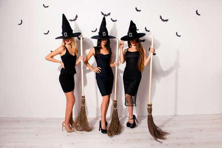 Volledige lengte van een groep van drie mysterieuze verborgen vampiermonsters uit de maitresse in elegante kostuumkleding, met felrode lippen, lange tovenaarshoofddeksels, serieus, met bedekte duivelsogen, met bezems