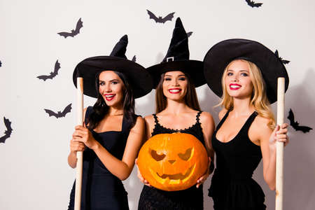 Group of three flirty coquettes in masquerade elegant dresses, with red lips, cutted decorative jack-o-lantern, in dark headwear, on white wall`s background with scary small creatures vampires Stock fotó