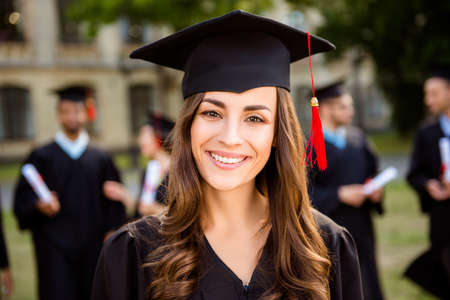 Happy cute brunette caucasian grad girl is smiling, her class mates are behind. She is in a black mortar board, with red tassel, in gown, with nice brown curly hair. Master degree! Success! Stock Photo