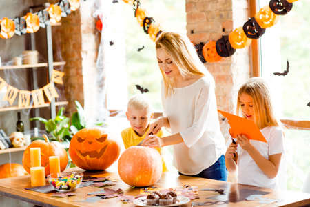 Halloween mood. Blonde family of mother and two siblings are preparing for party, cutting decorations, making jackolantern, desktop with candles, candies, fall leaves, little black bats on windows