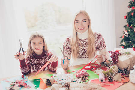 Small lovely cheerful blonde with her mom are doing handcraft activity. Desktop full of tapes, pine-cones, sketches, presents boxes, ready for x mas noel. Happiness and motherhood concept