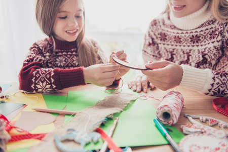 Happiness, upbringing, childhood, friendship, leisure, traditions x mas noel concept. Close up cropped of lovely blonde with her mommy doing handcraft activity, enjoying, desktop is full of materials 스톡 콘텐츠