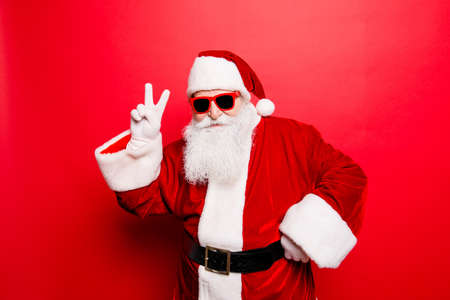 Cool funny playful naughty tourist santa grandfather showing peace signs, fooling around, in trendy specs, so confident. Stockfoto
