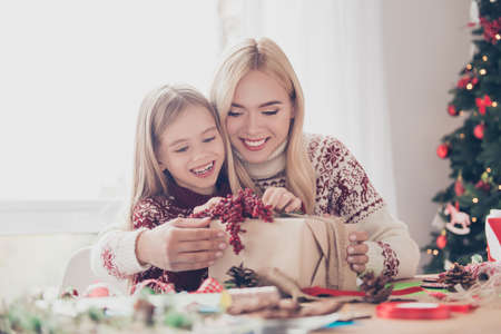 Happiness, upbringing, leisure, friendship, childhood, hobby, x mas, noel concept. Little lovely blonde with her mom are organising design of gift, enjoying using rope, ribbon, tape, firtree near