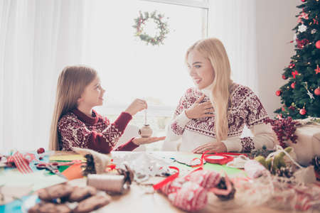 Desktop full of handcraft activity supplies, small lovely blonde haired kid presents her mum a diy, ready for x mas noel, sunshine in window, happiness, upbringing, motherhood concept