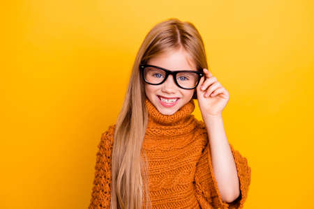 Health care, clear vision, specs, lenses pre teens concept. Close up portrait of charming blonde schoolgirl in fashionable black frames, knitted handmade warm outfit, intelligent and smiley Stock fotó - 87597841