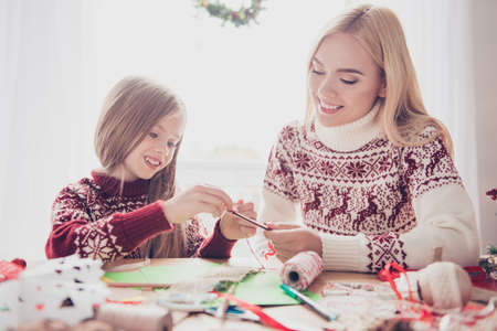 Lovely blonde with her mommy doing handcraft activity, enjoying. Happiness, upbringing, childhood, friendship, leisure, traditions x mas, noel concept, desktop full of materials