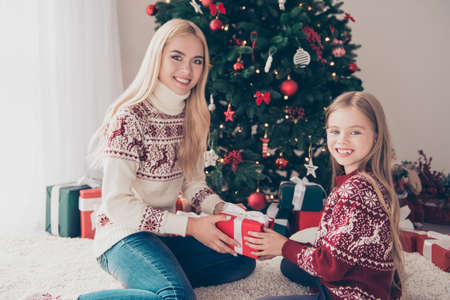 X mas, noel, traditions, maternity, motherhood. Little lovely blonde is taking wrapped surprise with tape bow from her mum, both in knitted cute traditional clothing, so adorable