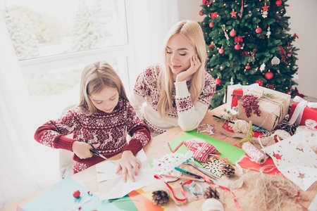Little, lovely, cheerful blonde with her mom are doing handcraft activity. Desktop full of tapes, pine-cones, ribbons, presents boxes, ready for x mas noel. Happiness and motherhood concept Stock Photo