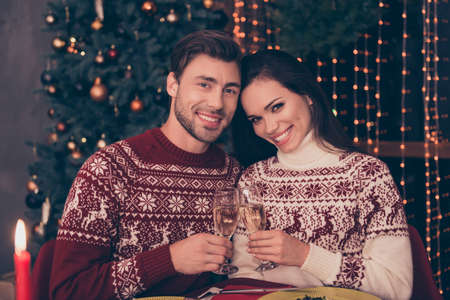 Festive friends with stemware of martini embrace sitting at x mas fest, in knitted cute traditional x mas costumes with ornament, enjoy, firtree, garland, night, candle, sparkles, true feelings