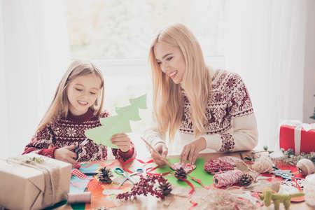 Kleine, lieve, vrolijke blonde prinses met haar moeder doet ambachtelijke activiteiten. Desktop vol spullen, scharen, potlood, tapes, linten, dennenappels, presenteert dozen, klaar voor x mas noel