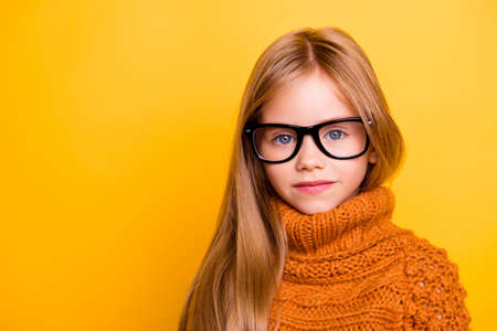 Health care, eyeball check, clear vision, youngsters concept. Close up portrait of charming blonde schoolgirl in fashionable black specs, knitted handmade warm outfit, intelligent and concentrated Stock Photo