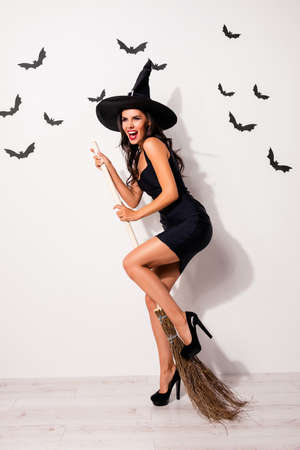 Full-length of mysterious playful, mystical gorgeous satanic bad fairy enchantress, hot figure, slim body, fashionable dark dress, shows teeth and prepared to take off on broom stick, white background Stock Photo