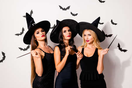 Diabolic, satanic, devil, hex, wiccan exorcist paranormal, dark spirits culture concept. Three hot flirty serious coquettes sorceress supersition spiritualists on white background with bats Standard-Bild