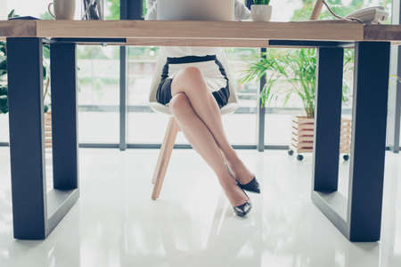 Close up cropped photo of attractive legs of the elegant stunning business lady in dark high hills shoes, skirt, she is sitting in the moden office, trendy chair and desk, shuining white floor Stock Photo