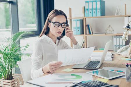 重要な情報について話す彼女の pda の礼装は、とてもスタイリッシュな光のモダンなデザインのオフィスで彼女の職場で座っての成功したエレガント 写真素材