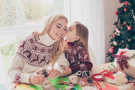 Little lovely blonde with her mommy are hugging, doing handcraft activity. Desktop full of tapes, ribbons, treats, papers, presents boxes, ready for x mas noel, traditions, maternity, motherhood Stock Photo