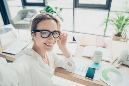 Successful charming relaxed brown haired economist with hairdo is making photo on camera, taken at her work station in smart outfit, black trendy eyewear, serene, carefree mode