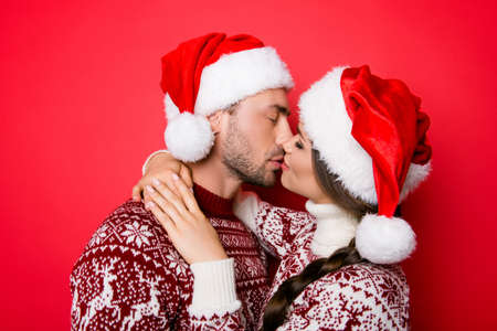 cute guy: Side-view profile portrait of adorable sweet family embracing and kissing each other with such love and care, in knitted cute traditional x mas wear with ornament, lady has braided  brunette hair