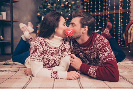 cute guy: Closeup low angle of adorable dreamy sweet cute friends kissing behind tasty yummy treat with bow on stick, lying down on floor on plaid, carpet, winter feast, coziness, warm, in socks, pine tree Stock Photo