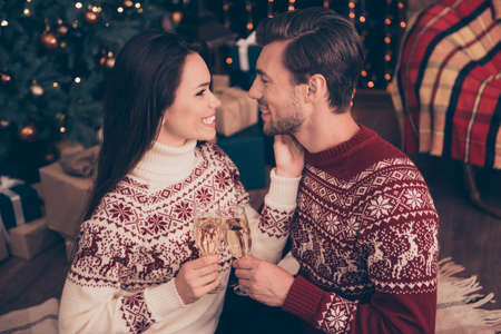 Festive friends with stemware of martini embrace bonding, so excited in knitted cute traditional x mas costumes with ornament, enjoy, look in eyes of each other, december time, firtree, garland, night