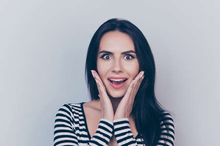 Very excited lady in casual wear, gesturing unbelievable unexpected wonderment, expressing positive emotions, with wide open eyes and mouth, on pure lght grey background, holding her face with arms Stock fotó