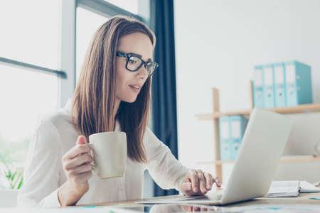 形式的な摩耗の明るいモダンなデザインのオフィスで彼女の職場で座っているの成功した茶色髪エコノミスト専門家の肖像画に近い焦点を当てて報 写真素材