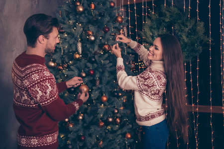 Cheerful husband and wife with long brunette hair are so excited setting the decorative firtree, knitted cute traditional x mas costumes with ornament, jeans, enjoy, garland of sparkles on window
