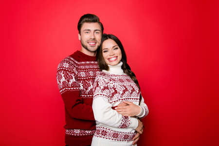 Adorable sweet caucasian couple is bonding, so excited in knitted cute traditional x mas costumes with ornament, cuddle, enjoy, guy hugs lady from behind, she has a toothy grin