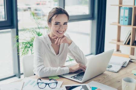Desarrollo, autoridad, concepto de feminidad. La mujer de negocios bonita se está sentando en su estación de trabajo moderna ligera, comprobando correos electrónicos delante del dispositivo digital, sonriendo y mirando la cámara Foto de archivo