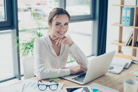 Development, authority, feminity concept. Pretty business woman is sitting at her light modern work station, checking e mails in front of digital device, smiling and looking at camera