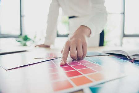 Creatieve bezigheid. Sluit omhoog van hand van vrouwelijke grafische ontwerper, binnenlandse ontwerper, architect, stilist, kiest zij de kleuren voor nieuw project, stoppend haar aandacht op purpere
