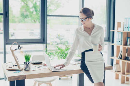 Successful feminine brown haired economist professional in formal wear, sitting on top of her desk at work place in a light modern design office, making report, focused and drink beverage