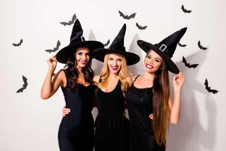 Group of three cute embracing seductive worlocks in carnival dresses, so slim and playful, with red lips, beaming smiles, in dark headwear, white wall background, scary small creatures vampires