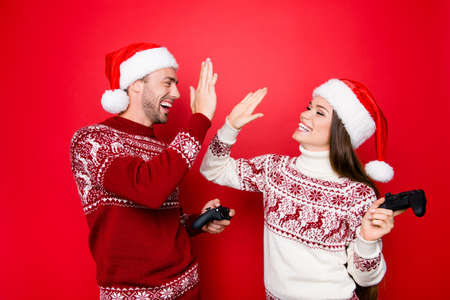 Happiness, winter, chill, december, noel, mode. Excited married couple in traditional x mas head wear are making high five, winning at crazy play station competition, grin and laugh Stock Photo - 87597943