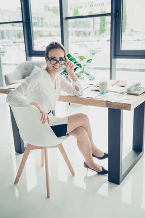 Successful charming relaxed brown haired lawyer is enjoying beverage at her work station, in smart outfit, black trendy eyewear, so serene, carefree, resting mode