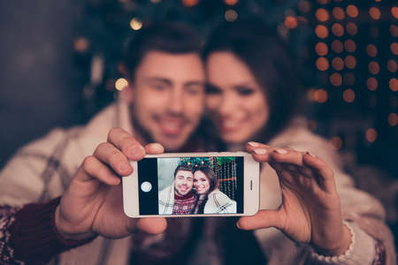 Cheerful husband and wife are photographers for their portrait. Not clear shot of them bonding hug embrace, lights on background, taking it on telephone, focus on smart pda, vague visual effects