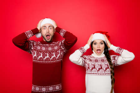 Omg! Increadible unbelievable crazy discount gifts time! Holly jolly x mas is soon! Be ready, prepare! Two young shocked lovers are amazed with wide open eyes, mouthes, holding head with arms