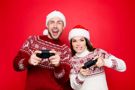 December noel, funky, happiness, carefree mode. Excited married couple in knitted traditional x mas wear with ornament, head wear are holding joy sticks and playing videogames, grin and laugh