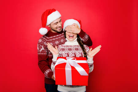 X mas promotion and miracle sale time! Cheerful partner in knitted clothing, head wear is closing his lady eyes with palm on arm, she has braided brunette hair, holding wrapped box with tape