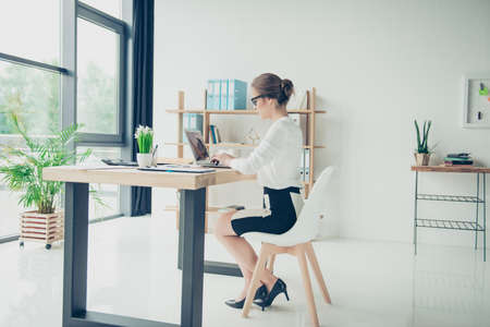 Full length side shot of gorgeous business lady, sitting at her light modern work station, checking reports on her digital device, in trendy specs, with hairdo. Development, authority, feminity Stock Photo