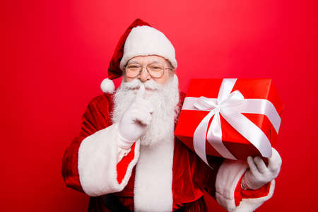 Shh! Keep secret. No sound mute silent confidential, privacy quiet, shush hissing hush concept. Funny Saint Nicholas with forefinger by his lips, holding gift. Festive holly jolly x mas noel Stok Fotoğraf